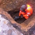 an image of a worker laying a pipe underground