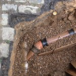 an image of an underground pipe submerged in gravel