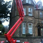 an image of a fully extended cherry picker outside a period home