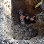 an image of a hole in the ground with two pipes