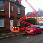 an image of a cherry picker being used to reach the roof of a house